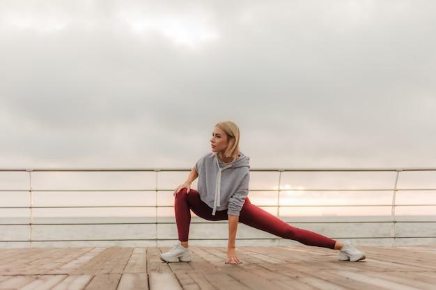 Ochtend training gezonde levensstijl concept jonge aantrekkelijke vrouw in sportkleding doet been strekken voordat u gaat sporten op het strand bij zonsopgang
