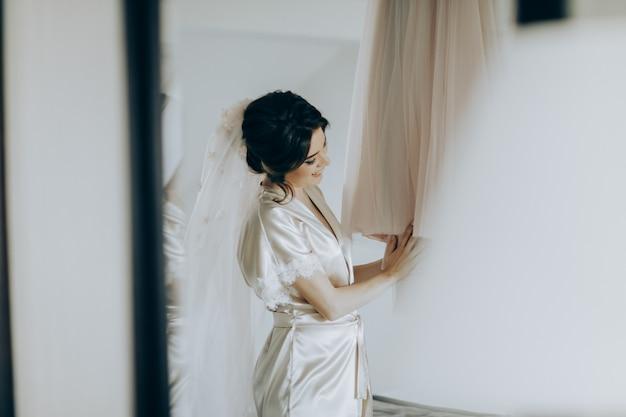 Ochtend van de bruid. bruidsprijzen. de bruid bewondert en raakt haar jurk aan