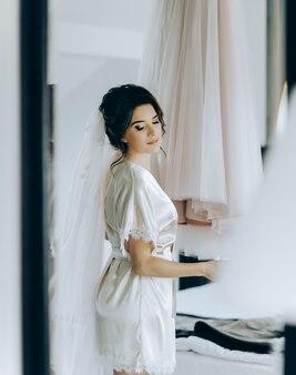 Ochtend van de bruid. de bruid bewondert en raakt haar jurk aan