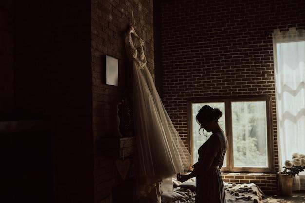 Ochtend van de bruid. de bruid in gewaad kijkt naar de trouwjurk.