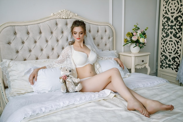 Ochtend van de bruid. de bruid zit op het bed. het mooie sexy blondemeisje stellen in wit kantondergoed.