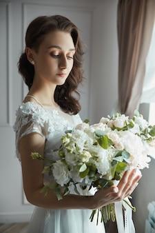 Ochtend van de bruid. een mooie vrouw bereidt zich voor op een bruiloft, natuurlijke make-up en een chique kapsel