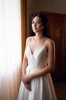 Ochtend van de bruid, een vrouw die zich voorbereidt op de huwelijksceremonie, gelukkige emoties voor de bruiloft