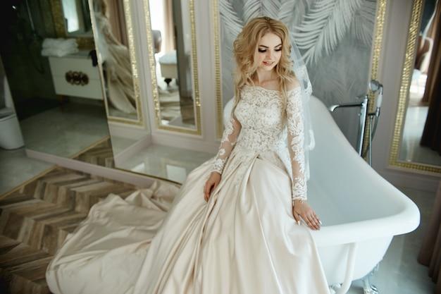 Ochtend van de bruid. een vrouw in een trouwjurk in de badkamer