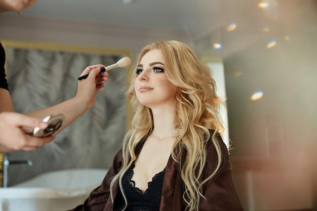 Ochtend van de bruid. een vrouw in lingerie die make-up doet om zich klaar te maken voor de bruiloft