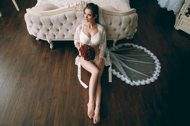 Ochtend van de bruid. het mooie sexy blondemeisje stellen in wit kantondergoed