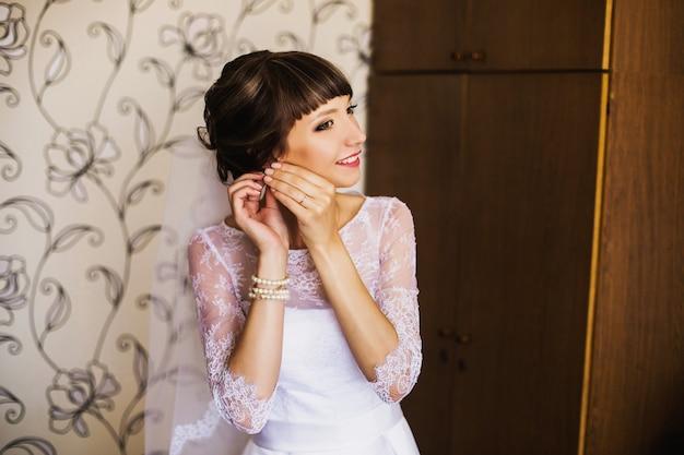 Ochtend van de bruid. huwelijksceremonie. het meisje in een witte jurk en sluier. kleding aantrekken. vrouwelijk portret