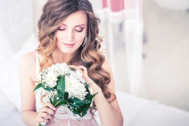 Ochtend van de bruid in een mooie lichte studio met bloemen.