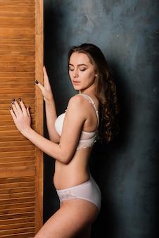 Ochtend van de bruid. sexy meisje poseren in wit kanten ondergoed. portret van een mooie jonge vrouw in een wit ondergoed. verleidelijke vrouw in wit linnen en peignoir.