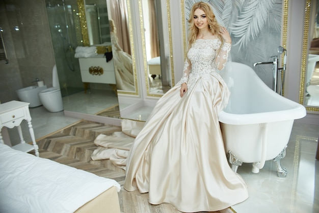 Ochtend van de bruid-vrouw in trouwjurk in de badkamer