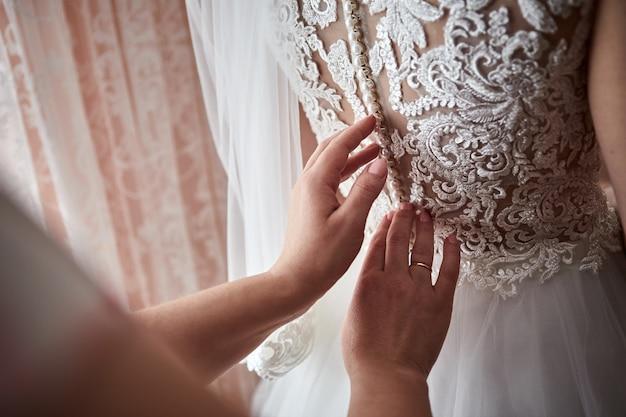 Ochtend van de bruid wanneer ze een mooie jurk draagt, vrouw die zich klaarmaakt voor de huwelijksceremonie
