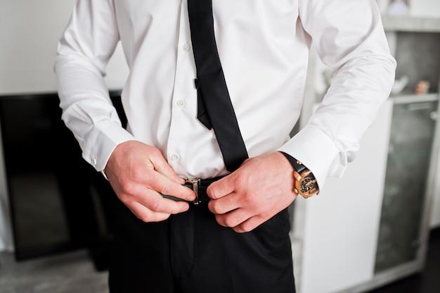 Ochtend van de bruidegomvoorbereiding. jonge en knappe bruidegom aankleden. bind riem.