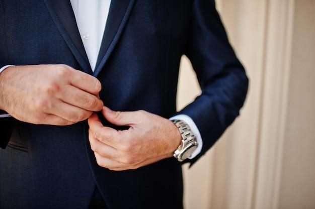 Ochtend van de bruidegomvoorbereiding. jonge en knappe bruidegom aankleden.