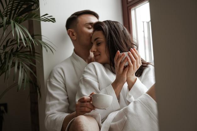 Ochtend van gelukkig jong stel in witte badjassen thuis zittend op het raam, koffie drinken en knuffelen.