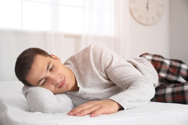 Ochtend van jonge man liggend op bed met zachte matras Premium Foto