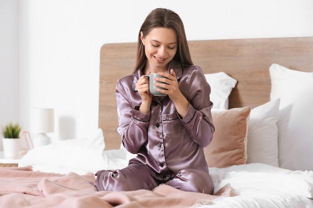 Ochtend van mooie jonge vrouw koffie drinken in de slaapkamer