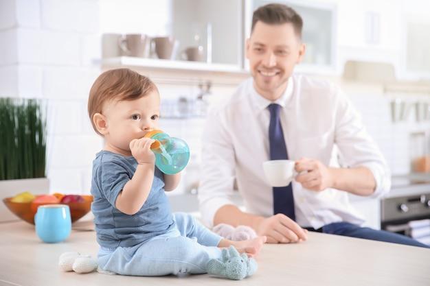 Ochtend van schattige babyjongen en zijn vader in de keuken