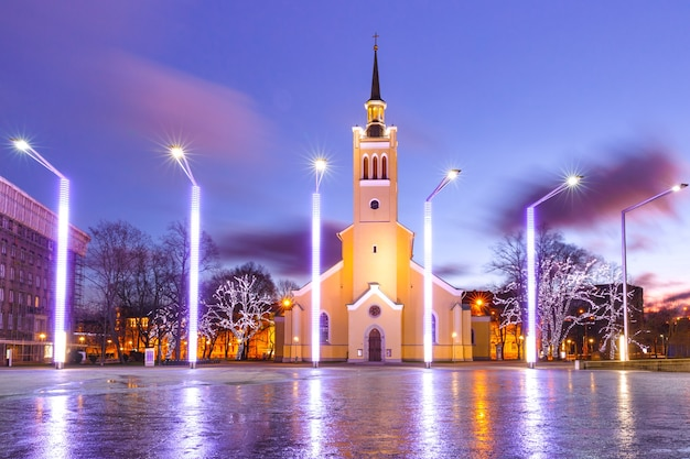 Ochtend versierd en verlicht christmas freedom square met st. john's church van tallinn bij zonsopgang, estland
