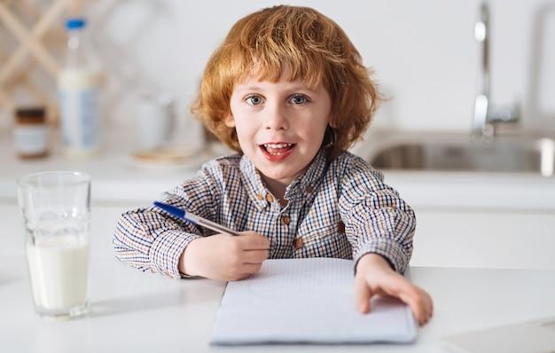 Ochtend vogel. leuk lief slim kind zit aan de helder witte tafel en schrijft iets op terwijl een glas melk naast hem op de tafel staat