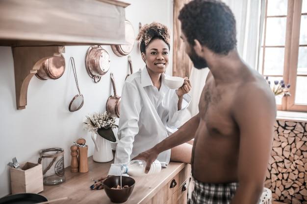 Ochtend, vrije dag. jonge donkere vrouw in wit overhemd koffie drinken en man voorbereiding ontbijt met melk praten in de keuken