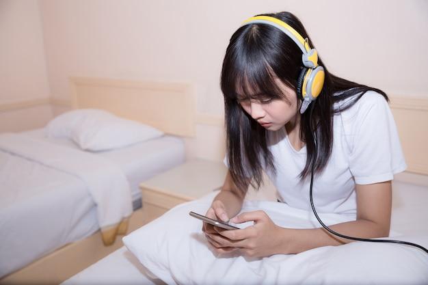 Ochtend, vrije tijd, kerstmis en mensenconcept - gelukkige jonge vrouw in bed thuis slaapkamer