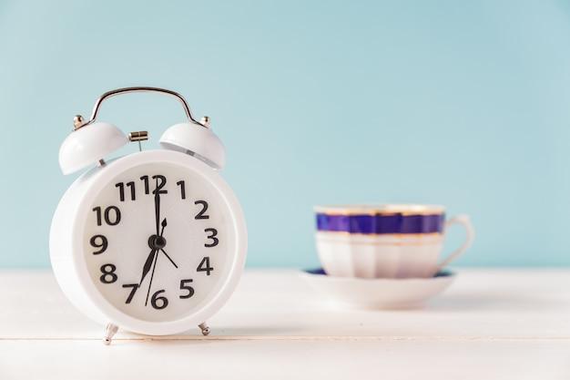 Ochtend wakker worden. witte wekker en kopje thee of koffie op witte tafel met kopie ruimte.