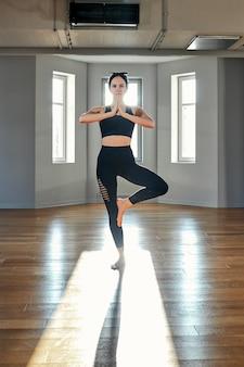 Ochtend yoga meisje doet rekoefeningen in de kamer voor pilates. prachtig licht, luchtfoto's, een gezonde levensstijl, lichaamshormonen en ziel, verlichting, kopieerruimte.