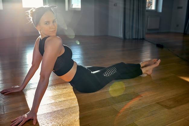 Ochtend yoga meisje doet rekoefeningen in de kamer voor pilates. prachtig licht, luchtfoto's, een gezonde levensstijl, lichaamshormonen en ziel, verlichting