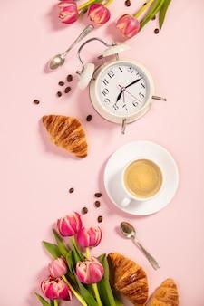Ochtendkoffie, croissants, wekker en roze tulpen. plat leggen