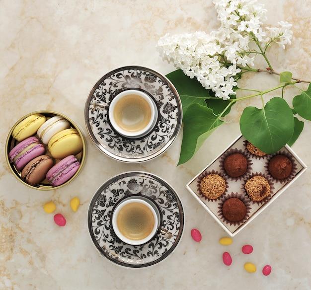 Ochtendkoffie met cakes macarons en een tak van sering