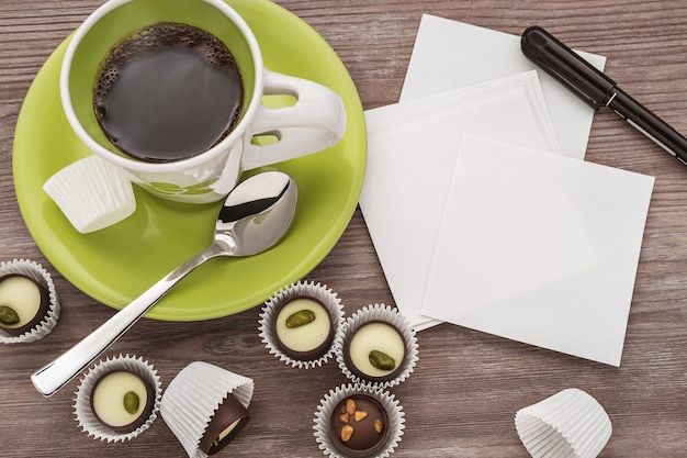 Ochtendkoffie met chocolaatjes en schone vellen papier voor aantekeningen