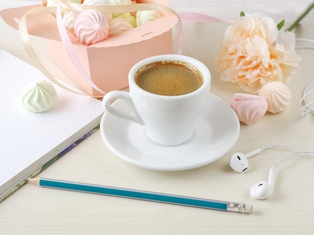 Ochtendkoffie met een notitieboekje en een doos die met kleine schuimgebakjes op een houten lichte achtergrond wordt gevuld