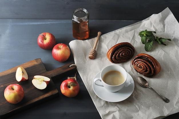 Ochtendkoffie met koffie en broodjes met maanzaad, appels en honing