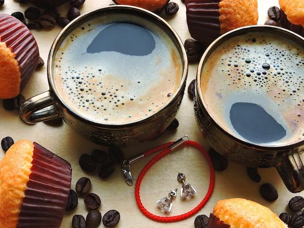 Ochtendkoffie, mini-muffins en een rode armband met oorbellen als geschenk. concept een valentijnsdagvergadering.
