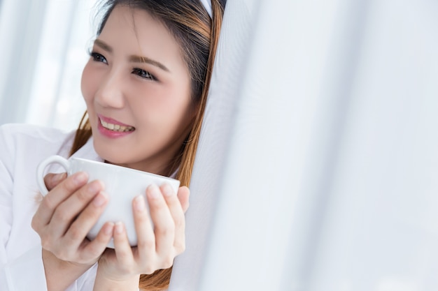 Ochtendkoffie, toevallige levensstijl van aziatische vrouw naast het venster.