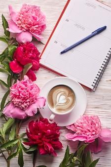 Ochtendkoffiemok voor ontbijt, leeg notitieboekje, potlood en roze pioenbloemen op witte stenen tafelbladweergave in platliggende stijl.