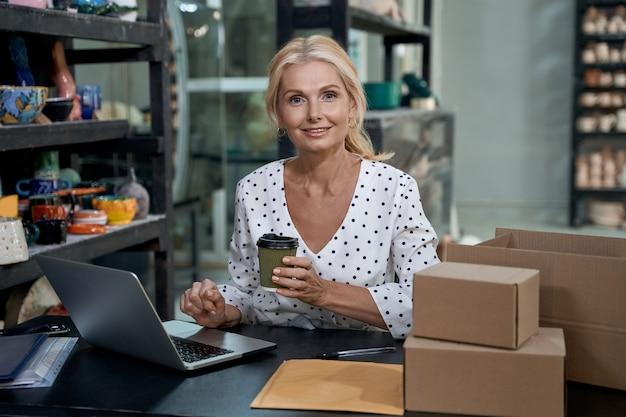 Ochtendkoffieportret van mooie vrouwelijke bedrijfseigenaar of zakenvrouw die aan laptop werkt in
