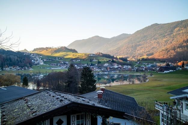 Ochtendlandlandschap met traditionele huizen, velden en bergen op een achtergrond van heldere hemel in oostenrijk.