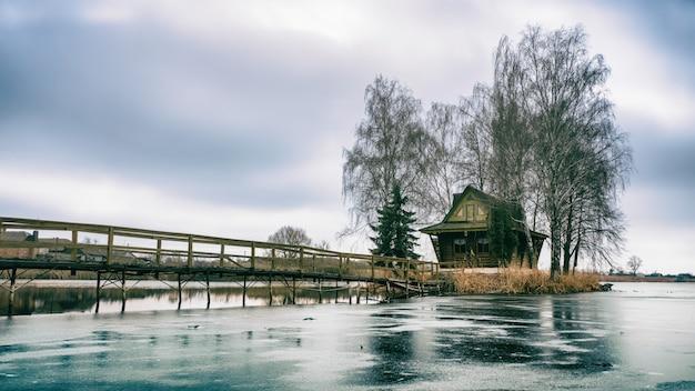 Ochtendlandschap, houten jachthuis, op een klein kunstmatig eiland. een houten platform komt naar het huis, berkenbomen groeien aan beide kanten