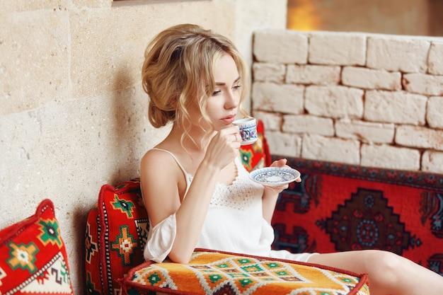 Ochtendmeisje het drinken koffie rustende zitting op een turkse bank. vrouw dromen, mooi blond kapsel, hete thee in een beker in haar handen