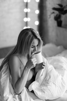 Ochtendmeisjes de blonde met kopje thee koffie ontbijt op bed ik ben net wakker geworden