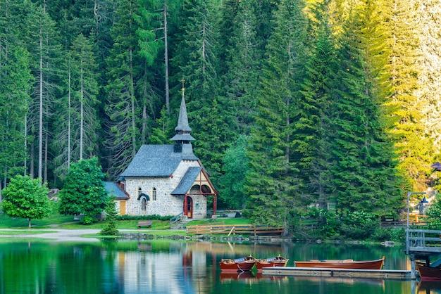 Ochtendmening van kleine oude kerk aan de oever van het meer van braies in zuid-tirol, italië