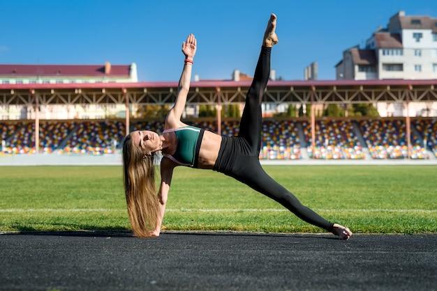 Ochtendoefeningen op het stadion. jonge, sportieve en slanke vrouw die oefeningen maakt