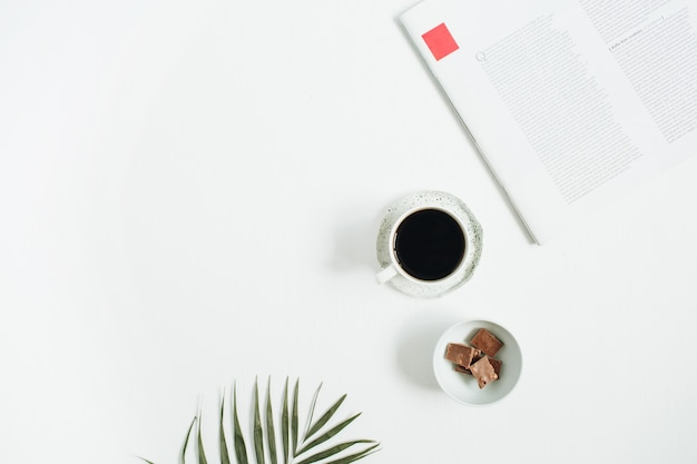 Ochtendontbijt met koffiekop en chocolade met tropisch palmblad en tijdschrift op wit