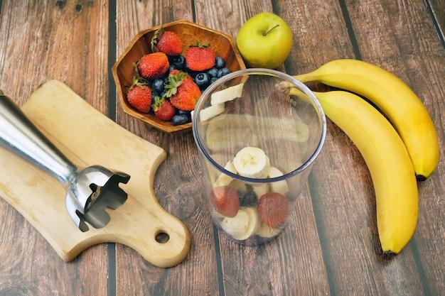 Ochtendontbijt met vers fruit en yoghurt op een achtergrond van sappige bananen en bessen