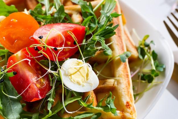 Ochtendontbijt met zelfgemaakte wafels, gesneden ei, verse biologische tomaten en rucola op een plaat.