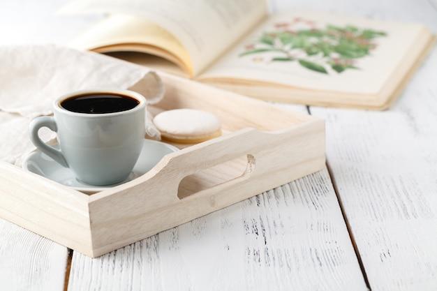 Ochtendontbijt, mok met koffie, boek op een houten dienblad