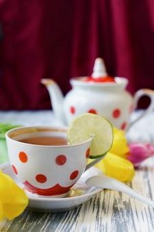 Ochtendontbijt van thee in een kop kleurrijke erwten met roze bloemen