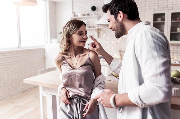 Ochtendpret. leuke langharige jonge vrouw met mooie make-up die gelukkig glimlacht terwijl het hebben van ochtendpret met haar echtgenoot