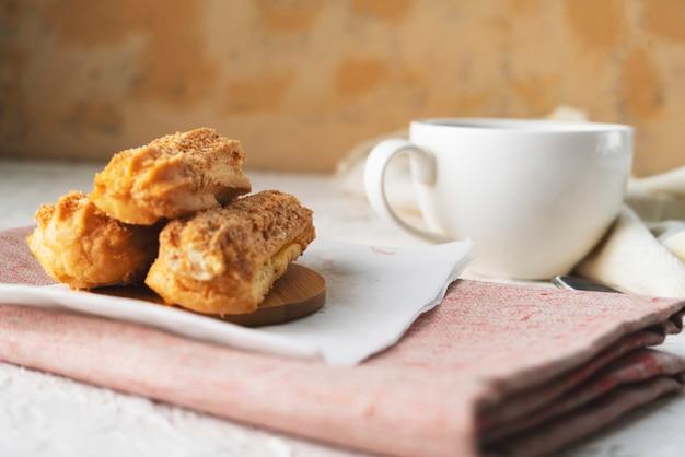Ochtendsnack met koffie en romige eclair op een tafel met wit tafelkleed, zakelijk ontbijt